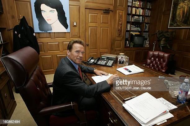 Rendezvous With Arnold Schwarzenegger Attitude souriante d'Arnold SCHWARZENEGGER en costume d'homme d'affaires travaillant à son bureau de gouverneur...