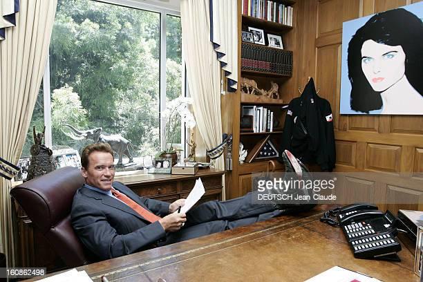 Rendezvous With Arnold Schwarzenegger Attitude souriante d'Arnold SCHWARZENEGGER en costume d'homme d'affaires et santiags de cowboy les pieds posés...