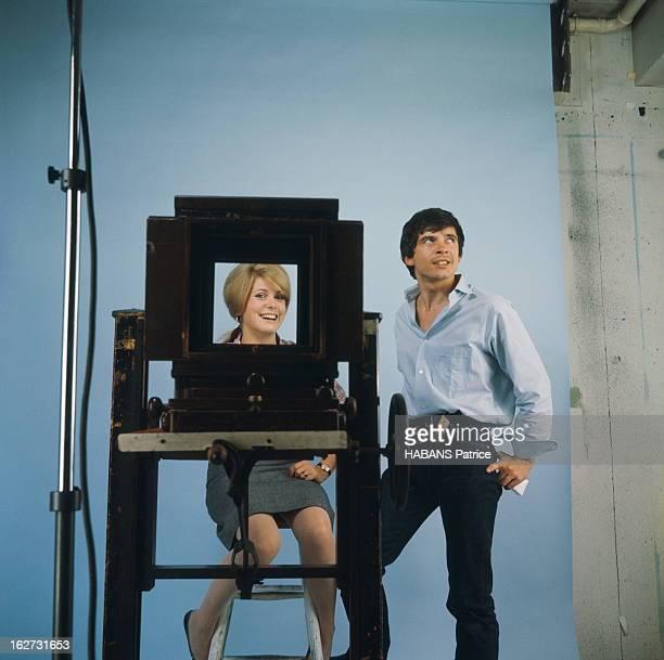 Rendezvous With Catherine Deneuve And David Bailey Photo studio attitude souriante de Catherine DENEUVE assise sur un tabouret vue à travers une...