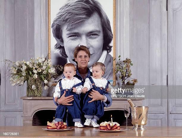 Rendezvous With Catherine Pironi And Her Twins Gilles And Didier. Rambouillet - 23 décembre 1988 - Chez elle, devant un grand portrait de son mari...