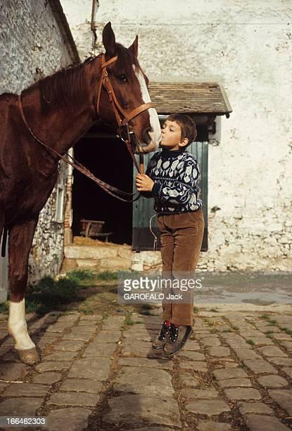 Rendezvous With Cecile Aubry And Her Son Sebastian France 1965 Portrait de SEBASTIEN en pull fantaisie et pantalon de velours brun sautant à pieds...