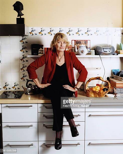 Rendezvous With Claire Bretecher At Home In Paris Attitude of the designer Claire BRETECHER sitting on a table in his kitchendining room with a...