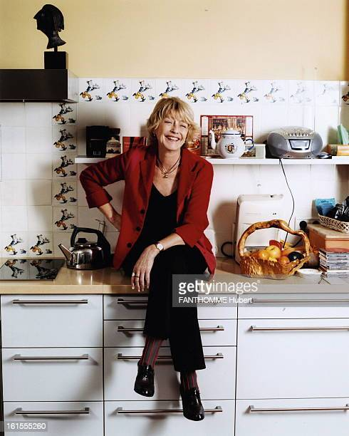 Rendezvous With Claire Bretecher Attitude of the designer Claire BRETECHER sitting on a table in his kitchendining room with a frieze of decor for...