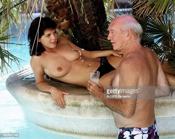 Rendezvous With Eddie Barclay In SaintTropez Eddie BARCLAY de profil un verre à la main debout dans la piscine auprès de sa compagne Caroline GIGANTI...