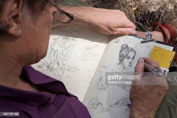 Rendezvous With Gerard And Elisabeth Garouste On Holiday Gérard GAROUSTE dessinant dans un cahier de croquis dont il ne se sépare le portrait d'une...