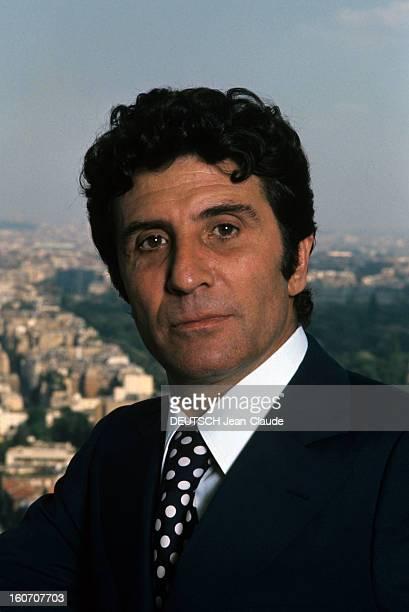 Rendezvous With Gilbert Becaud Portrait de Gilbert BECAUD en costume noir et chemise blanche avec cravate noire à pois blancs sur la terrasse de son...