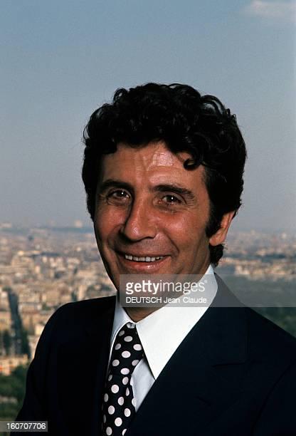 Rendezvous With Gilbert Becaud Portrait de Gilbert BECAUDsouriant en costume noir et chemise blanche avec cravate noire à pois blancs sur la terrasse...