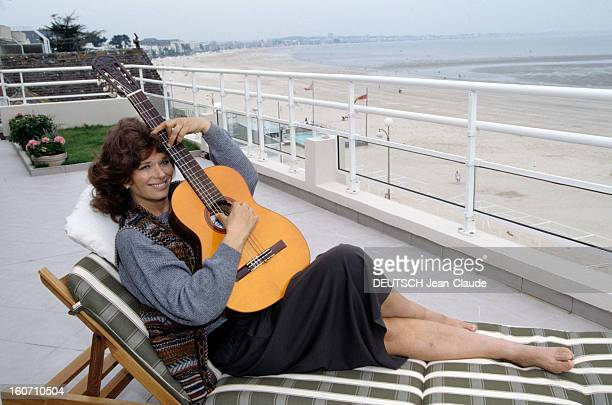 Rendezvous With Lea Massari And Her Husband Carlo Bianchini A La Baule Léa MASSARI allongée dans une chaise longue jouant de la guitare