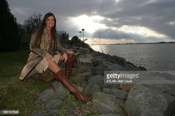 Rendezvous With Lynda Lemay In Canada Attitude souriante de Lynda LEMAY assise sur un rondin de bois au bord de l'eau en jupe courte et cuissardes...
