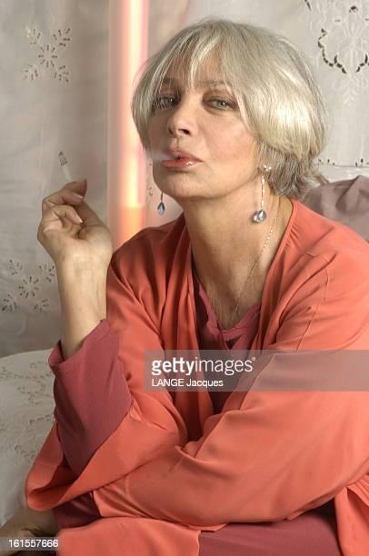 Rendezvous With Marie Laforet Plan de face souriant de Marie LAFORET recrachant la fumée de sa cigarette chez elle à PARIS