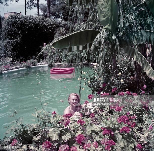 Rendezvous With Martine Carol In Rome A Rome l'actrice Martine CAROL dans l'eau d'une piscine entourée de végétation appuyée contre le rebord