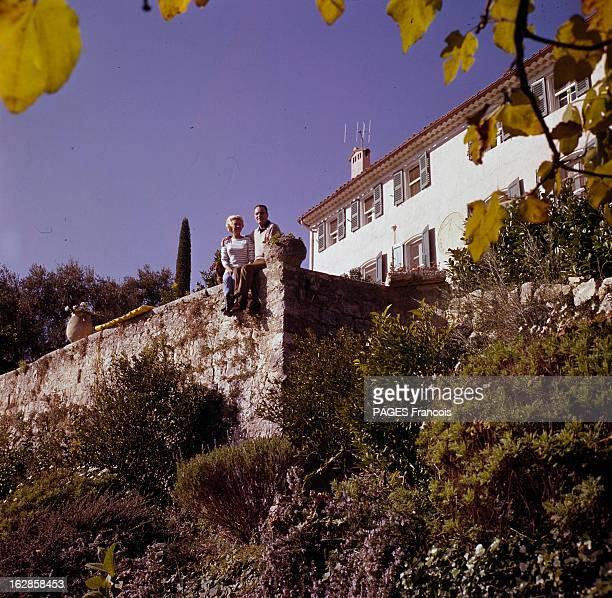 Rendezvous With Martine Carol Martine CAROL et son mari le docteur André ROUVEIX assis sur le muret d'une terrasse de maison entourée de végétation