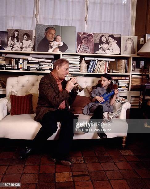 Rendezvous With Michel Serrault With Familly Michel SERRAULT chez lui à Neuilly jouant du cornet pour sa petitefille Gwendoline 6 ans et demi tous...
