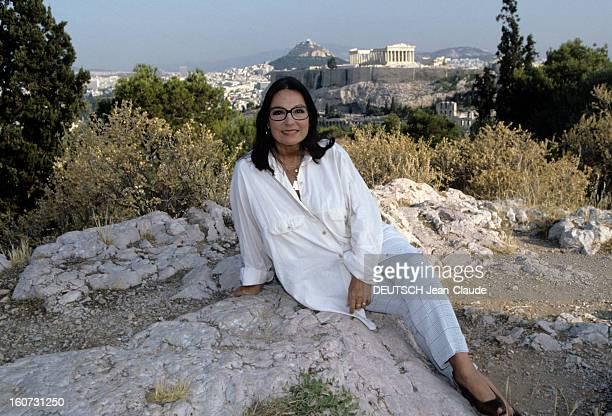 Rendezvous With Nana Mouskouri A Athènes chez elle Nana MOUSKOURI posant assise sur un rocher