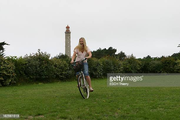 Rendezvous With Natasha Regnier On Holiday In Britain Attitude souriante de Natacha REGNIER faisant du vélo à BELLEILE un phare en arrière plan