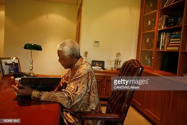 Rendezvous With Nelson Mandela In Johannesburg Attitude de Nelson MANDELA de profil assis dans le bureau de sa fondation à JOHANNESBURG feuilletant...