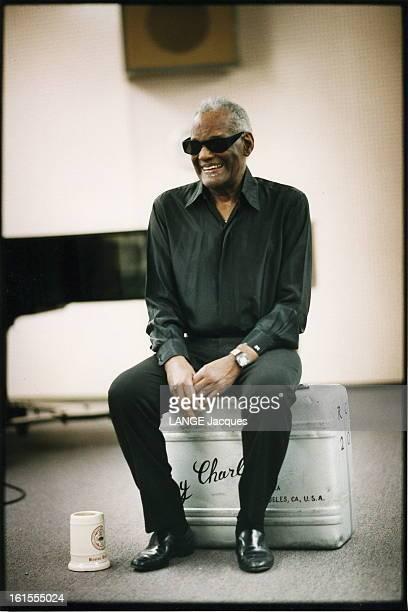 Rendezvous With Ray Charles In Los Angeles Attitude souriante de Ray CHARLES assis sur une valise de musicien marquée à son nom chez lui à LOS ANGELES