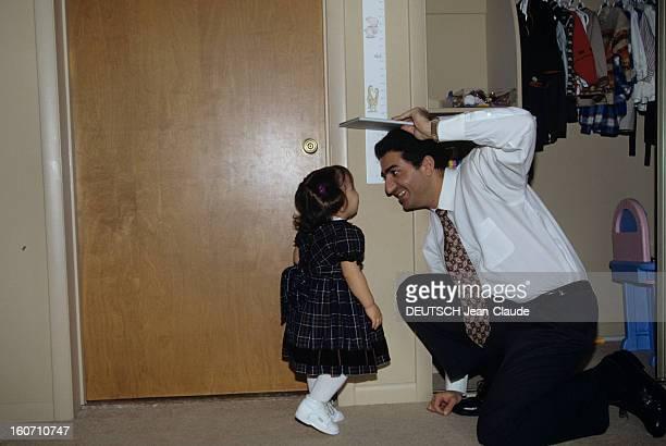 Rendezvous With Reza Pahlavi Ii And His Family A Washington dans sa résidence REZA PAHLAVI II accroupi sous une toise jouant avec une de ses filles