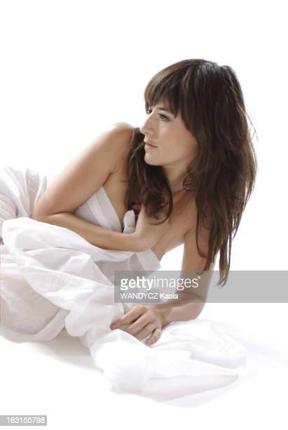 Rendezvous With Romance Bohringer Photo studio attitude sensuelle de Romane BOHRINGER de profil allongée par terre nue serrant contre sa poitrine un...