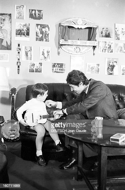 Rendezvous With Sacha Distel With Family. Paris - 3 octobre 1968 - Portrait du chanteur Sacha DISTEL en costume-cravate, assis sur le canapé de son...