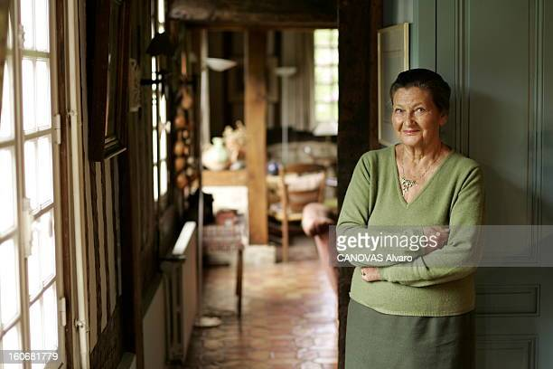 Rendezvous With Simone Veil In Normandy. Plan de face souriant de Simone VEIL, bras croisés, appuyée contre un mur dans sa maison de NORMANDIE.
