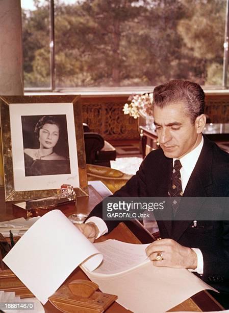 Rendezvous With The Shah Of Iran Portrait du Shah d'Iran veste noire sur chemise blanche et cravate assis à son bureau et feuilletant des documents