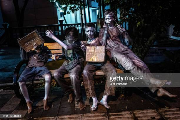 """Rendi , Adit , Aril , Angga , wearing silver paint beg on the street on March 11, 2021 in Depok, Indonesia. 'Silver Men', called """"Manusia Silver"""" in..."""
