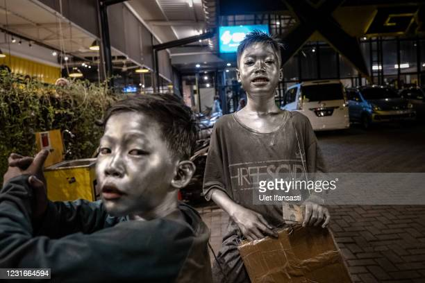 """Rendi and Aril , wearing silver paint beg on the restaurant on March 11, 2021 in Depok, Indonesia. 'Silver Men', called """"Manusia Silver"""" in..."""