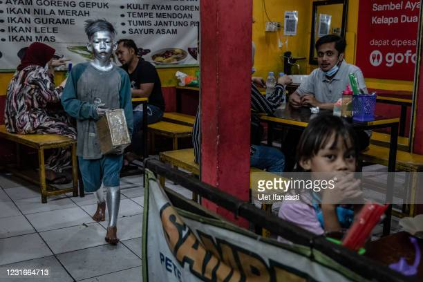 """Rendi , wearing silver paint beg on the restaurant on March 11, 2021 in Depok, Indonesia. 'Silver Men', called """"Manusia Silver"""" in Indonesian..."""