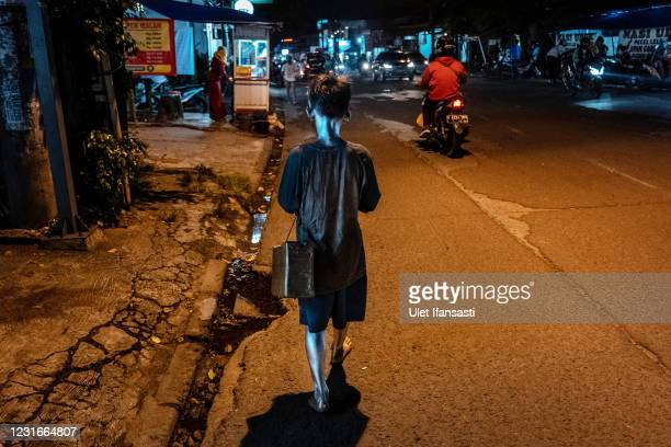"""Rendi , wearing silver paint walk as he beg on the street on March 11, 2021 in Depok, Indonesia. 'Silver Men', called """"Manusia Silver"""" in Indonesian..."""