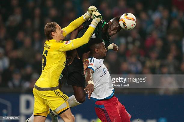 Rene Adler and Johan Djourou of Hamburg and Salif Sane of Hannover compete for the ball during the First Bundesliga match between Hamburger SV and...