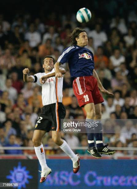 Rene Aufhauser of Salzburg goes for a high ball against Edu of Valencia during the third qualifying round of the UEFA Champions League match at the...