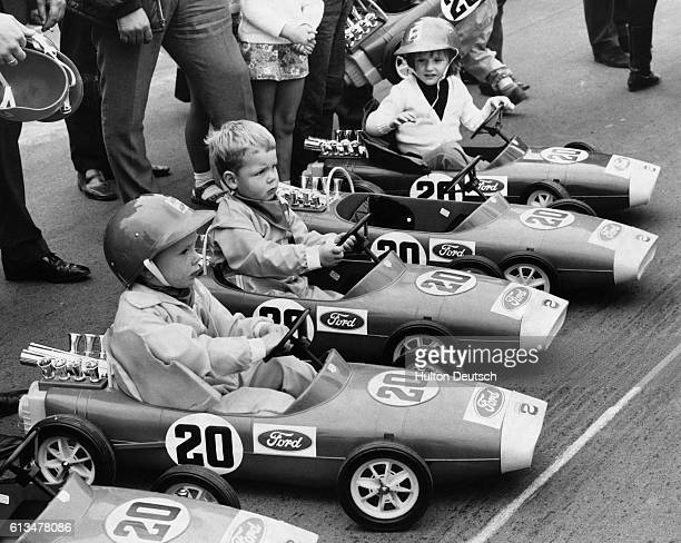 Rene Belso aged 5 with Roger Duckworth aged 4 and Amanda McLaren aged 3 1/2 seated behind the wheels of miniature pedaldriven LotusFord racecars at a...