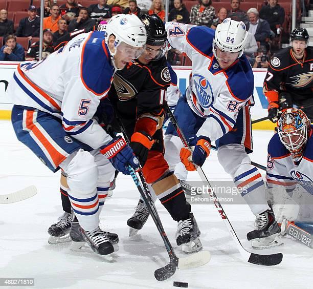 Rene Bourque of the Anaheim Ducks battles for the puck against Oscar Klefbom and Mark Fayne of the Edmonton Oilers on December 10 2014 at Honda...