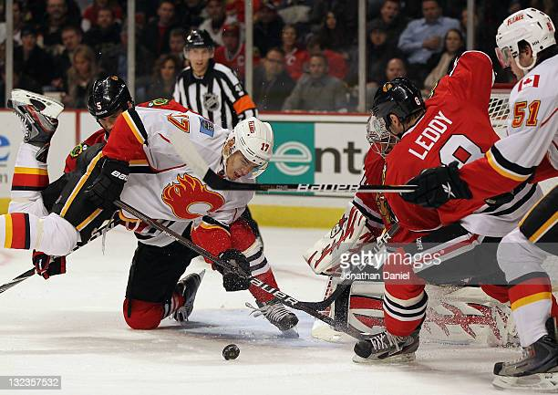 Rene Bourque of the Calgary Flames falls trying to shoot the puck against Ray Emery and Nick Leddy of the Chicago Blackhawks at the United Center on...