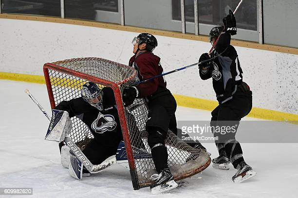 Rene Bourque of the Colorado Avalanche is checked into the net by Duncan Siemens as Nathan Lieuwn takes cover during the first day of training camp...