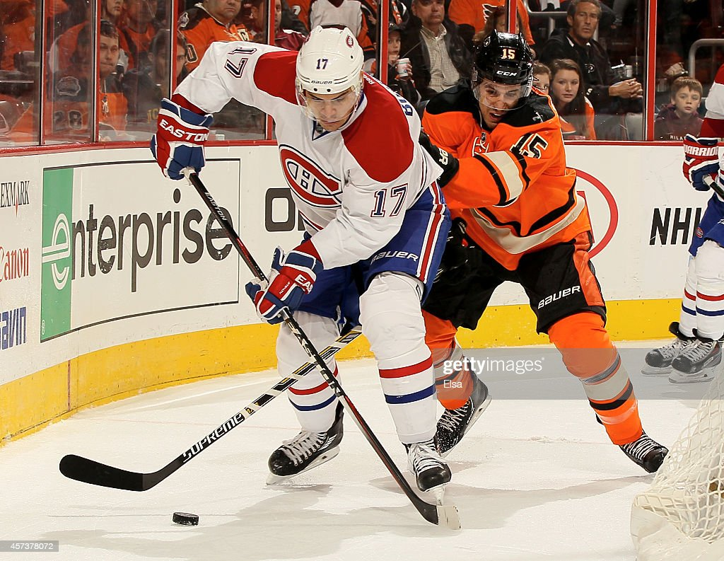 Rene Bourque #17 of the Montreal Canadiens and Michael Del Zotto #15 of the Philadelphia Flyers fight for the puck on October 11, 2014 at the Wells Fargo Center in Philadelphia, Pennsylvania.The Montreal Canadiens defeated the Philadelphia Flyers 4-3 in an overtime shootout.