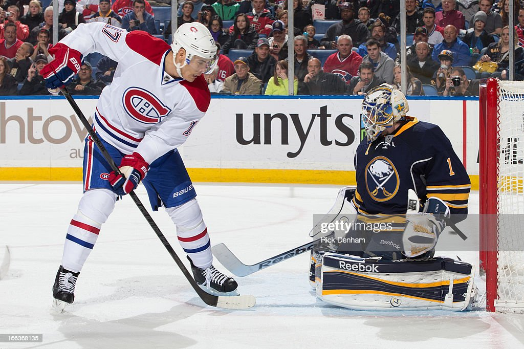 Rene Bourque #17 of the Montreal Canadiens looks for a loose puck in front of Jhonas Enroth #1 of the Buffalo Sabres during the NHL game at First Niagara Center on April 11, 2013 in Buffalo, New York.