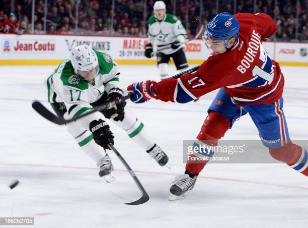Rene Bourque of the Montreal Canadiens slaps a shot while being challenged by Rich Peverley of the Dallas Stars during the NHL game on October 29...