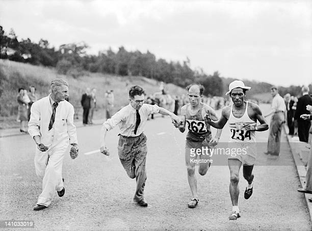 Rene Josset of France and Eusebio Guinez of Argentina are handed wet sponges to cool them down along the Barnet bypass during the marathon event at...
