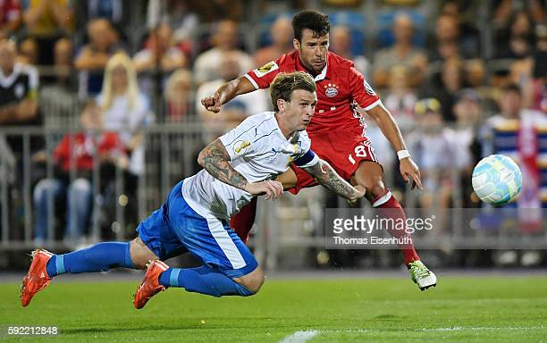 Rene Klingbeil of Jena is challenged by Juan Bernat of Munich during the DFB Cup match between FC Carl Zeiss Jena and Bayern Muenchen at...