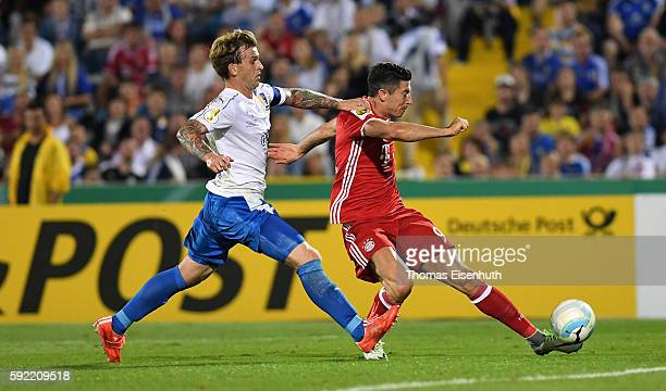 Rene Klingbeil of Jena is challenged by Robert Lewandowski of Munich during the DFB Cup match between FC Carl Zeiss Jena and Bayern Muenchen at...