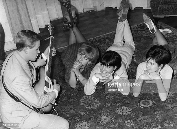 Rene Kollo *Musiker Sänger Tenor D spielt EGitarre in einer Wohnungvor ihm auf dem Teppich liegenbewundernd drei junge Frauen 1961anhänger fans...