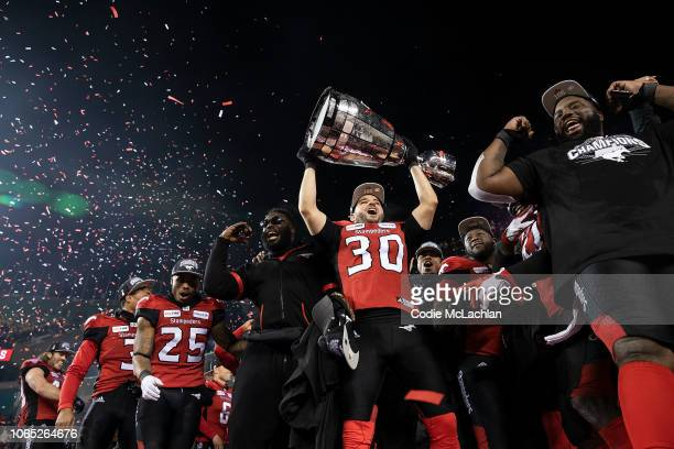 Rene Paredes of the Calgary Stampeders hoists the Grey Cup after their victory against the Ottawa Redblacks during the Grey Cup game at Commonwealth...