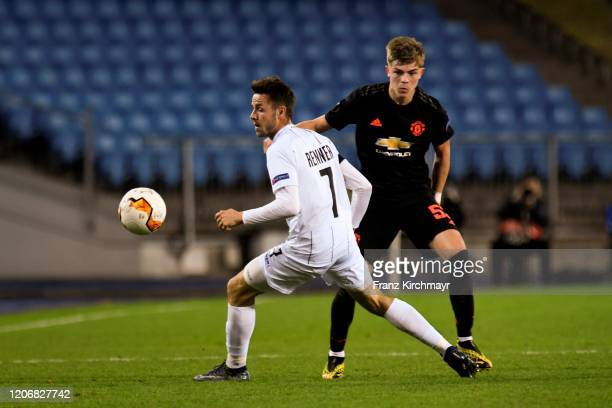 Rene Renner of LASK competes for the ball with Brandon Williams of Manchester United during UEFA Europa League Round of 16 First Leg match between...