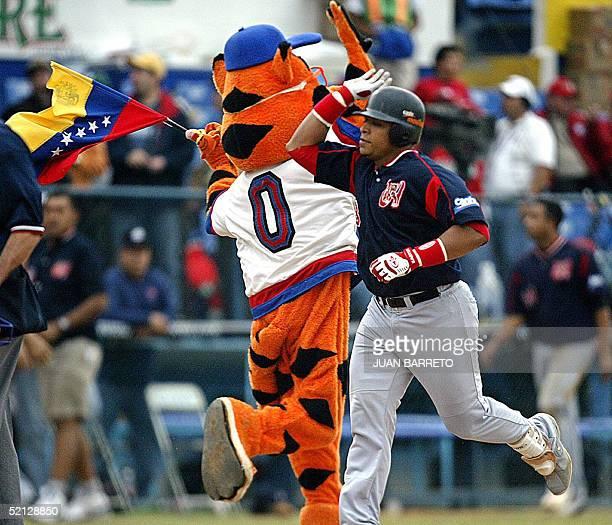 Rene Reyes de los Tigres de Aragua de Venezuela saluda a una mascota tras batear un home run en un juego contra Indios de Mayaguey de Puerto Rico...