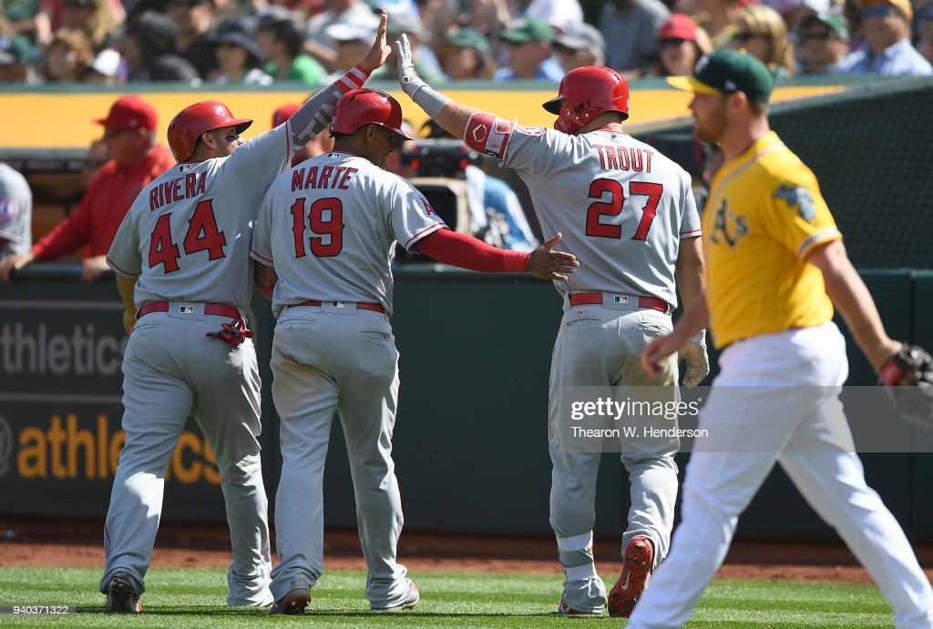 Rene Rivera #44 and Jefry Marte #19 of the Los Angeles Angels of Anaheim is congratulated by teammate Mike Trout #27 after they both scored on an rbi double from Zack Cozart #7 (not pictured) against the Oakland Athletics in the top of the six inning of a Major League baseball game at Oakland Alameda Coliseum on March 31, 2018 in Oakland, California.