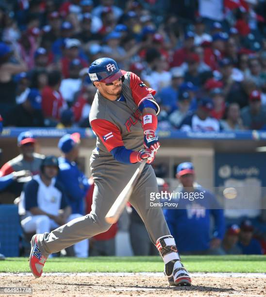 Rene Rivera of Puerto Rico hits an RBI double during the seventh inning of the World Baseball Classic Pool F Game Five between Puerto Rico and...