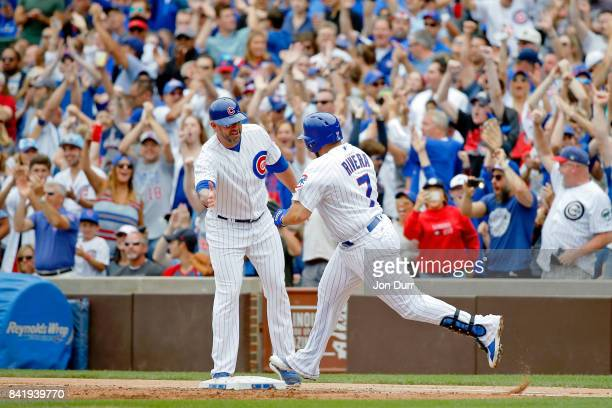 Rene Rivera of the Chicago Cubs high fives first base coach Brandon Hyde after hitting a grand slam against the Atlanta Braves during the second...