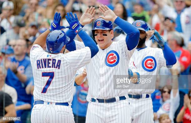 Rene Rivera of the Chicago Cubs is congratulated by Anthony Rizzo after hitting a grand slam against the Atlanta Braves during the second inning at...